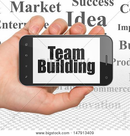 Business concept: Hand Holding Smartphone with  black text Team Building on display,  Tag Cloud background, 3D rendering