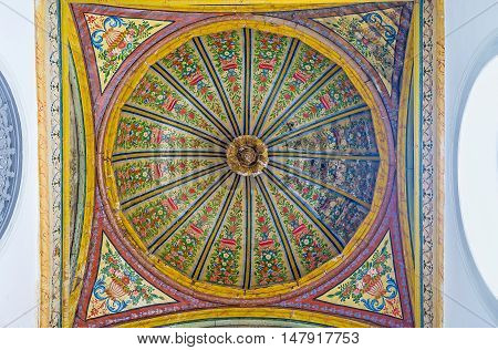 TUNIS TUNISIA - SEPTEMBER 2 2015: The colorful cupola over the staircase in Bardo National Museum decorated with floral painted patterns and carved details on September 2 in Tunis.