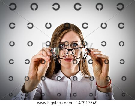 Woman in white is looking through the glasses. Oculist Ophthalmologist Doctor Point Examination Table.