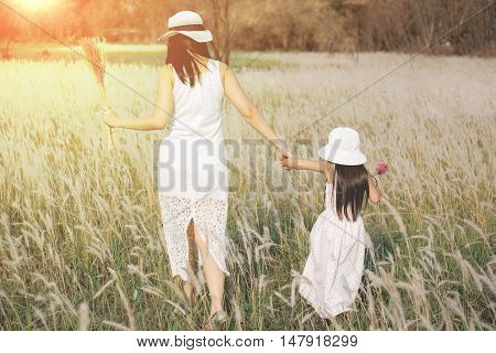 Portrait of beautiful happy smiling girl is with her mother to meadow outdoor in nature on sunny day