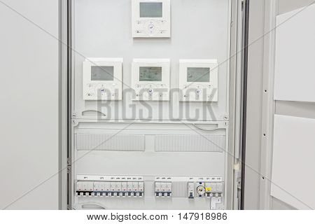 Smart home automation: display showing household consumptions related to temperature and heating. Automatic fuse electrical connector in power lines located inside of switch control panel board.