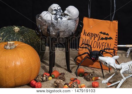 Table full of Halloween treats and decoration with spiders skeletons and pumpkins