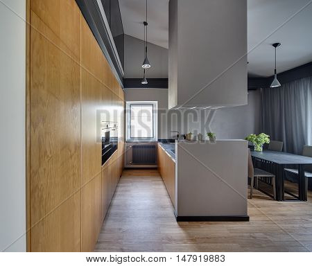 Kitchen in modern style with kitchen island with kitchen hood, table with chairs, windows with curtains and cupboard with built-in oven. On the floor there is a parquet. At the top there are lamps.