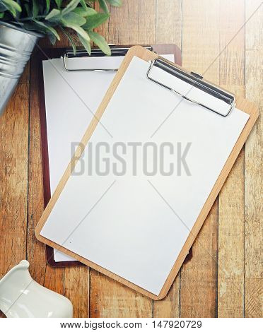 blank clipboard over wooden table ready for adding text. retro filtered image