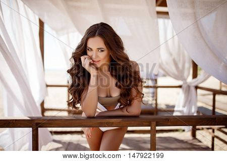 Portrait Of Attractive Brunette With Long Hair In White Bikini Posing At Wooden Tent With White Windy Curtains At Beach.