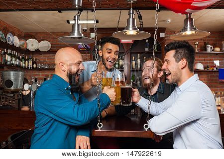 Man Group In Bar Clink Glasses Toasting, Drinking Beer Hold Mugs, Mix Race Cheerful Friends Wear Shirts Meeting Pub Communicate Talking