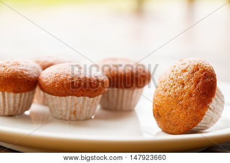 Banana muffin cake on white plate put on wooden table.