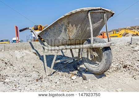 Wheelbarrow is filthy with dry cement. View on construction site. Landscape transform into urban area.