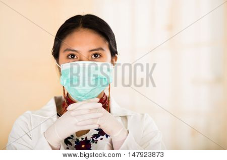 Young beautiful woman dressed in doctors coat and red necklace, face covered with facial mask looking into camera, egg white clinic background.