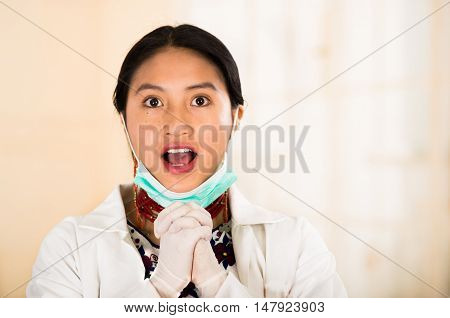 Young beautiful woman dressed in doctors coat and red necklace, facial mask pulled down to chin, smiling happily, egg white clinic background.
