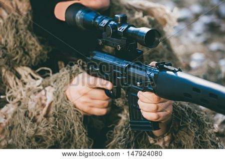 The soldier disguised in a balaclava and military camouflage aims at the sight of a sniper rifle. War Zone.