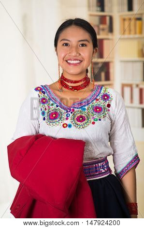 Beautiful young lawyer wearing traditional andean blouse, holding red jacket smiling to camera, bookshelves background.