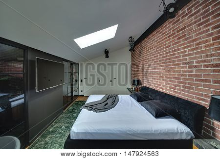 Contemporary bedroom with brick wall and parquet with green carpet on the floor. There is bed with pillows, racks with lamps and decorations, black wall with cupboards and TV, white wall with doors.