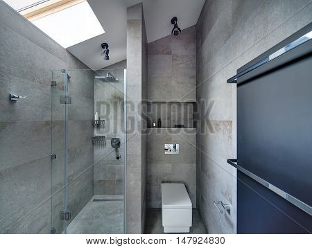 Bathroom in modern style with gray textured tiles on the floor and walls. There is shower with glass door, white toilet, black panel with two chrome towel rails. At the top there are lamps and window.