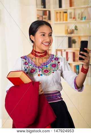 Beautiful young lawyer wearing traditional andean blouse with necklace, holding red jacket and book while using mobile phone, smiling happily, bookshelves background.