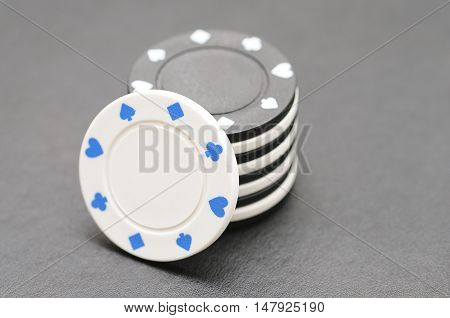 White and black poker chips on a black background
