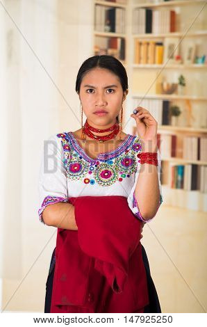 Beautiful young lawyer wearing black skirt, traditional andean blouse with necklace, standing posing for camera, holding red jacket, serious facial expression, bookshelves background.
