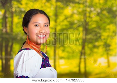 Beautiful young woman wearing traditional andean blouse with necklace, standing posing for camera, smiling happily, green forest background.