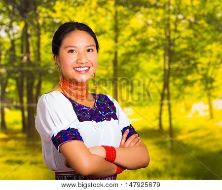 Beautiful young woman wearing traditional andean blouse with necklace, standing posing for camera, arms crossed smiling happily, green forest background.