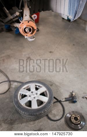 Brand new brake disc on car in a garage. Auto mechanic repairing a car.