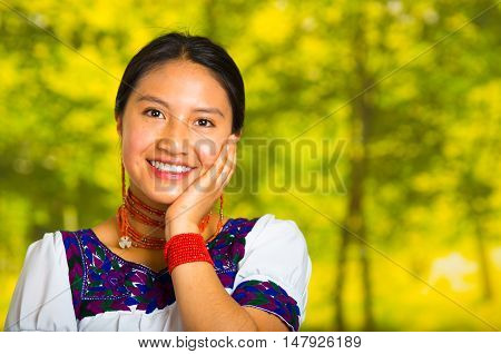 Headshot beautiful young woman wearing traditional andean blouse with red necklace, posing for camera touching face using hands while smiling happily, green forest background.