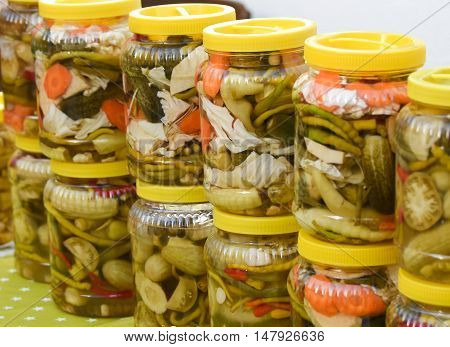Jars of pickled vegetables for sale at Turkish bazaar.  Jars with pickles, green tomatoes, pepper, cucumber, carrot.