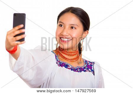 Beautiful young woman standing wearing traditional andean blouse and red necklace, holding mobile phone taking selfie while smiling happily, white studio background.