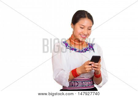 Beautiful young woman standing wearing traditional andean blouse and red necklace, holding mobile phone texting while smiling happily, white studio background.