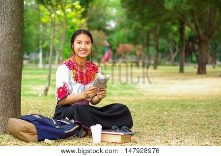 Young woman wearing traditional andean skirt and blouse with matching red necklace, sitting on grass next to tree in park area, relaxing while using tablet, smiling happily.