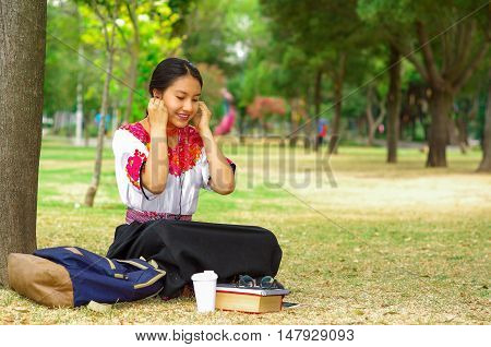 Young woman wearing traditional andean skirt and blouse with matching red necklace, sitting on grass next to tree in park area, relaxing while using mobile phone headphones connected, smiling happily.