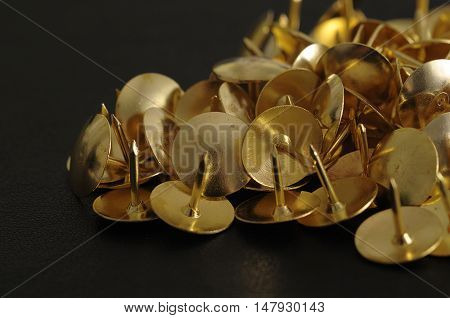 Bronze thumb tacks isolated on a black background