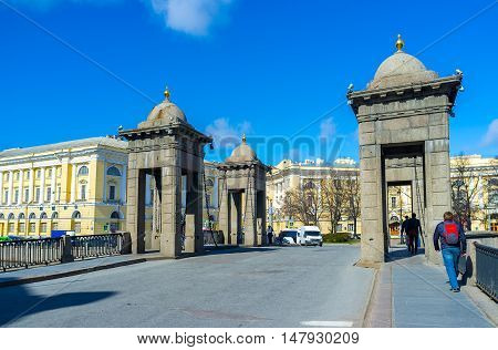 SAINT PETERSBURG RUSSIA - APRIL 25 2015: Four stone towers on Lomonosov Bridge with chains holding its movable parts on April 25 in Saint Petersburg.