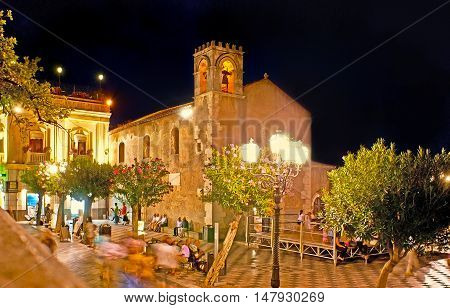 TAORMINA ITALY - OCTOBER 1 2012: The brightly illuminated medieval St Augustine Church located in Square of IX Aprile surrounded by benches outdoor cafes and bars full of tourists on October 1 in Taormina.