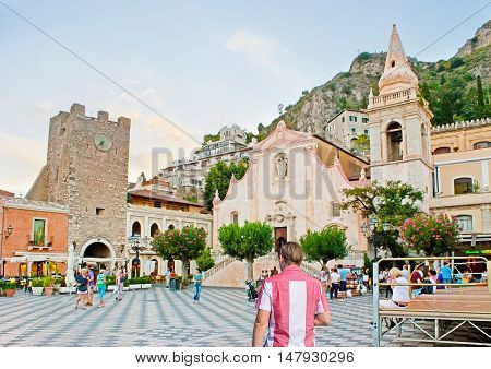 TAORMINA ITALY - OCTOBER 1 2012: The medieval Clock Tower and St Joseph Church located in the IX Aprile (Ninth of April) Square surrounded by cozy cafes taverns and souvenir stores on October 1 in Taormina.