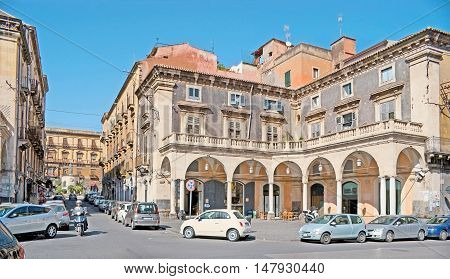 CATANIA ITALY - OCTOBER 10 2012: The old mansion with stores and workshops in arcades located in noisy street leading to the monument of Cardinal Giuseppe Benedetto Dusmet in San Francesco d'Assisi Square on October 10 in Catania.