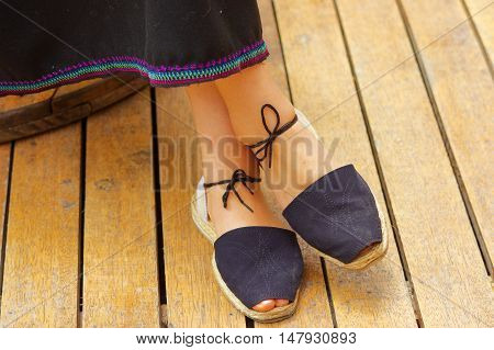 Closeup womans feet wearing simple traditional andean shoes, lace with knot tied around lower leg, legs crossed.