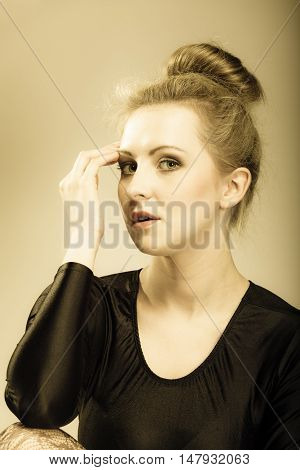 Portrait of young beautiful girl blonde woman makeup and hair bun vintage aged tone