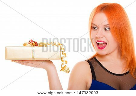 Christmas x-mas winter or valentine's day birthday concept - red hair wide eyed girl holding golden gift box studio shot isolated