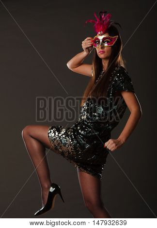 Holidays people and celebration concept. woman with carnival venetian mask sequin evening dress on gray background.