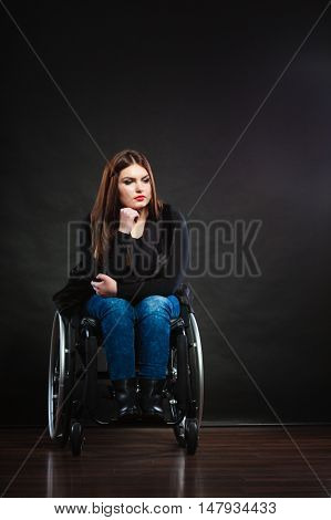 Sad girl sitting on wheelchair. Disabled depressed woman. Health medical disability rehabilitation concept.