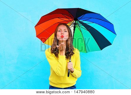 Pretty Young Woman With Colorful Umbrella Sends Air Sweet Kiss In Autumn Day Over Colorful Blue Back