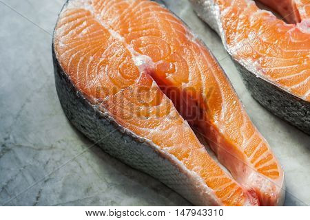 Two fresh raw salmon steaks on marble table. Selective focus. Close-up.