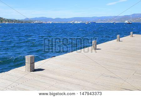 Wooden Boat Mooring Bollards On Jetty By Blue Ocean