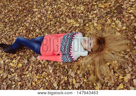 Fall concept - autumn woman laying in park. Beautiful young modern woman smiling happy and cheerful