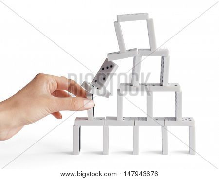 Woman hand build tower of dominoes, isolated on white