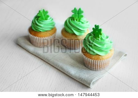 Tasty cupcakes with clover on napkin. Saint Patrics Day concept