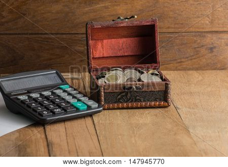 calculator with coin in a coffer on wood background