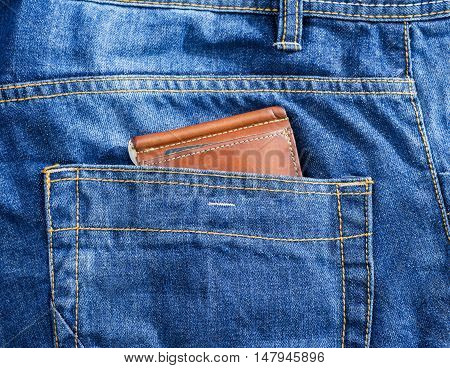 brown leather wallet in jeans back pocket blue