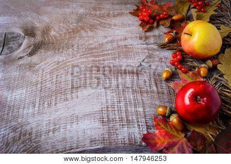 Border of apples berries and fall leaves on the rustic wooden background. Thanksgiving background with seasonal berries and fruits. Copy space