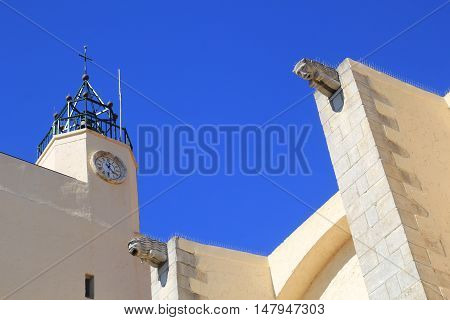 Gargoyles, Bell Tower And Clock Tower Against Blue Sky On A Church In The South Of France